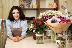Beau fleuriste de femme se tenant derrière le compteur photos stock