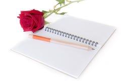 Beau fond de blanc de rose, de crayon et de carnet de rouge Image libre de droits
