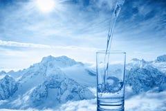 Beau fond de verser l'eau bleue en verre transparent Images libres de droits