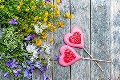 Beau fond du gisement de fleurs des marguerites et des cloches et de deux coeurs faits de caramel et massepain le jour du ` s de  Photographie stock