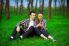 Beau fond du softCouple vert de fleurs de cerisier partageant des médias dans le téléphone intelligent se reposant sur l'herbe ve photos stock