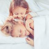 Beau frère et soeur se situant dans le lit à la maison Images libres de droits
