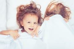 Beau frère et soeur se situant dans le lit à la maison Photo stock