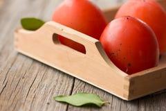 Beau fruit frais de kaki kaki mûr sur un fond en bois Le kaki a coupé en morceaux Plan rapproché Image libre de droits