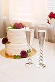 Beau gâteau blanc avec les roses rouges et deux verres avec le champagne Images stock