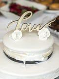 Beau gâteau de mariage avec de la crème avec amour des textes sur les roses supérieures de fleurs blanches Image stock