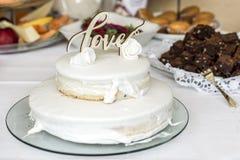 Beau gâteau de mariage avec de la crème avec amour des textes sur les roses supérieures de fleurs blanches Images stock