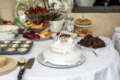 Beau gâteau de mariage avec de la crème avec amour des textes sur les roses supérieures de fleurs blanches Photographie stock libre de droits