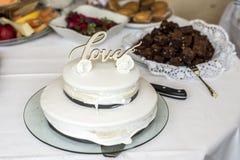 Beau gâteau de mariage avec de la crème avec amour des textes sur les roses supérieures de fleurs blanches Photographie stock