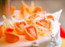 Beau gâteau de mariage dans des sons oranges Photographie stock