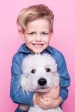 Beau garçon avec le caniche standard royal Portrait de studio au-dessus de fond rose Concept : amitié entre le garçon et son chie Photo stock