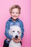 Beau garçon avec le caniche standard royal Portrait de studio au-dessus de fond rose Concept : amitié entre le garçon et son chie Photos libres de droits