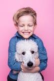 Beau garçon avec le caniche standard royal Portrait de studio au-dessus de fond rose Concept : amitié entre le garçon et son chie Photographie stock