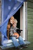 Beau garçon blond s'asseyant sur le filon-couche de fenêtre avec deux chiens et potirons de prise Image stock
