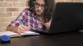 Beau garçon de l'adolescence avec les cheveux bouclés de brune travaillant sur son ordinateur portable et écrivant dans son carne banque de vidéos
