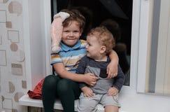 Beau garçon deux d'aspect européen s'asseyant sur le rebord de fenêtre Images libres de droits