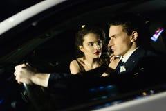 Beau garçon et fille s'asseyant dans la voiture, la réflexion de la rue dans le verre de la voiture Histoire d'amour Photo libre de droits