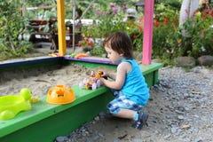 Beau garçon jouant avec le sable sur le terrain de jeu en été Photographie stock