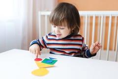 Beau garçon jouant avec les chiffres géométriques Photographie stock libre de droits
