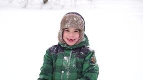 Beau garçon joyeux d'élève du cours préparatoire ayant l'amusement avec la neige Le pays des merveilles d'hiver banque de vidéos