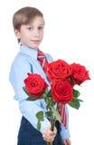 Beau garçon romantique portant une chemise et une cravatte étirant les roses rouges Photos libres de droits