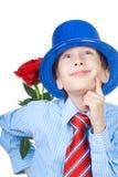 Beau garçon romantique utilisant une chemise, une cravate et le chapeau bleu tenant une rose Image libre de droits