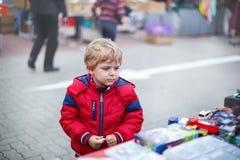 Beau garçon d'enfant en bas âge dans des vêtements rouges sur le marché aux puces. Image libre de droits