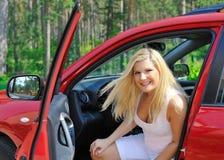 Beau gestionnaire de femme dans le véhicule brillant rouge Images libres de droits
