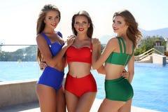 Beau girsl dans les swimsuites élégants colorés, posant près de la piscine Image libre de droits