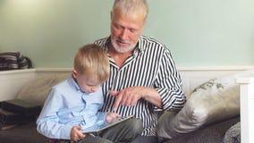 Beau grand-papa jouant avec son petit-fils sur le comprimé clips vidéos