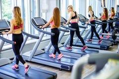 Beau groupe d'amis de jeunes femmes s'exerçant sur un tapis roulant au gymnase moderne lumineux Image stock