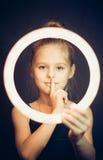 Beau gymnaste de jeune fille tenant un cercle rougeoyant et faisant le geste tranquille Photographie stock libre de droits