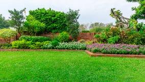 Beau jardin anglais de cottage, usine fleurissante colorée sur la pelouse lisse d'herbe verte et groupe d'arbres à feuilles persi image libre de droits