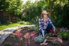 Beau jardinier féminin regardant l'appareil-photo souriant et jugeant la caisse en bois pleine des fleurs image libre de droits