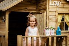 Beau jeu de fille avec la boîte d'arrosage dans une cabane dans un arbre Image libre de droits