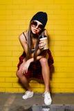 Beau jeune café sexy de boissons de fille et se reposer près du fond jaune de mur dans des lunettes de soleil, chemise de plaid r Photo libre de droits