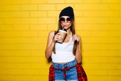 Beau jeune café de boissons de fille, souriant et posant près du fond jaune de mur dans des lunettes de soleil, chemise de p Images stock