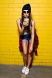 Beau jeune café sexy de boissons de fille, souriant et posant près du fond jaune de mur dans des lunettes de soleil, chemise de p Photos stock