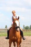 Beau jeune cheval blond de châtaigne d'équitation de femme Photographie stock