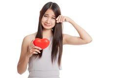 Beau jeune cri asiatique de femme avec le coeur rouge Image stock