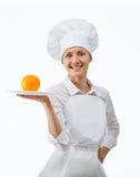 Beau jeune cuisinier féminin montrant l'orange d'un plat photos libres de droits