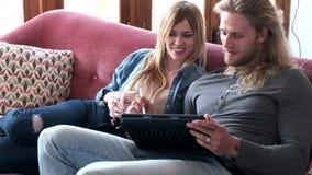 Beau jeune dessin de couples avec eux comprimé numérique tout en se reposant sur le sofa à la maison banque de vidéos