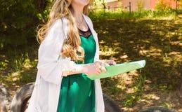 Beau jeune docteur féminin dans la robe médicale détenant les records médicaux Infirmière avec des rapports médicaux Photographie stock libre de droits