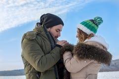 Beau jeune extérieur de couples dans les mains de chauffage d'hiver froid photos stock