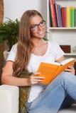 Beau jeune femme affichant un livre Photo stock