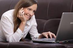 Beau jeune femme avec l'ordinateur portatif, téléphone portable et Photo stock