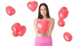 Beau jeune femme avec le ballon rouge de coeur Photographie stock