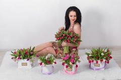 Beau jeune femme avec un bouquet des fleurs Images stock