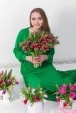 Beau jeune femme avec un bouquet des fleurs Image stock
