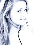 Beau jeune femme dans des sons bleus Image stock